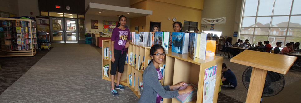 Four female students organizing books in the school's Learning Commons