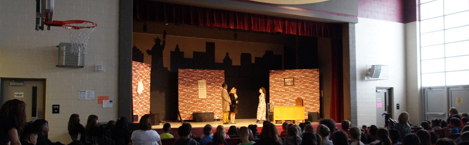Students on a stage acting in a gym